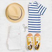 Child's striped t-shirt, demin shorts, accessories, yellow shoes and straw hat isolated on white background. Top view. Flat lay. Kid's summer clothes collage