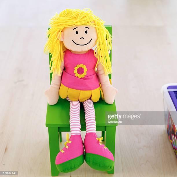 child's stuffed cloth doll sitting on green chair
