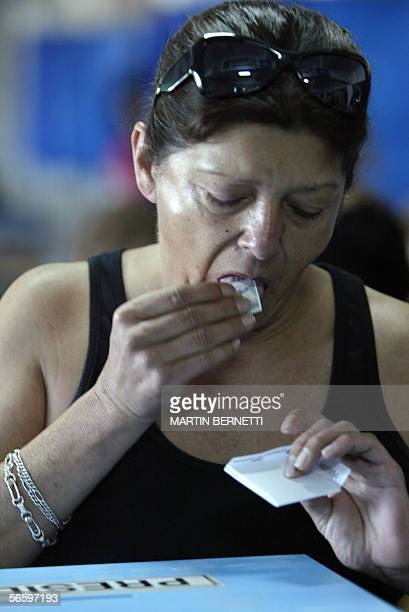 A woman licks a stamp to seal the voting envelope before casting her vote at a polling station in Santiago 15 January 2006 Chileans began casting...