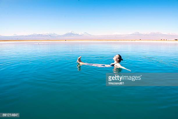 Chile, Atacama Desert, woman floating in the Laguna Cejar salt lake