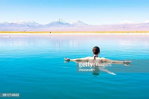Chile, Atacama Desert, woman floating in the Laguna Cejar salt lake