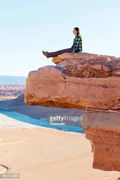 Chile, Atacama Desert, woman sitting on a cliff looking at view