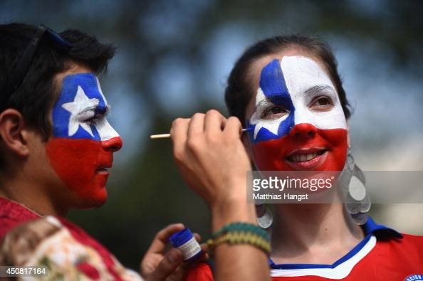 Chile fan has face paint applied prior to the 2014 FIFA World Cup Brazil Group B match between Spain and Chile at Maracana on June 18 2014 in Rio de...
