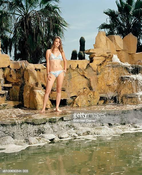 Chile, Iquique, young woman wearing bikini by fountain