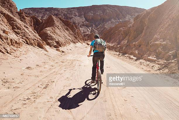 Chile, Man riding a mountain bike through the Valle de la Muerte, Atacama Desert