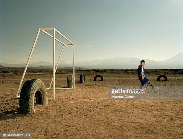 Chile, San Pedro de Atacama, boy (9-11) playing soccer in desert