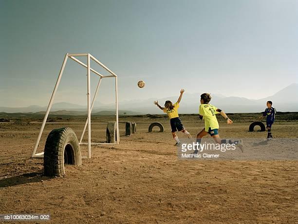 Chile, San Pedro de Atacama, boys (9-11) playing soccer in desert