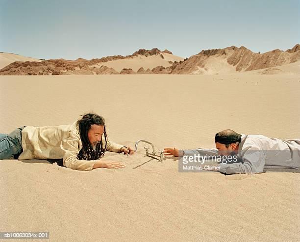 Chile, San Pedro de Atacama, two men reaching for tap in desert