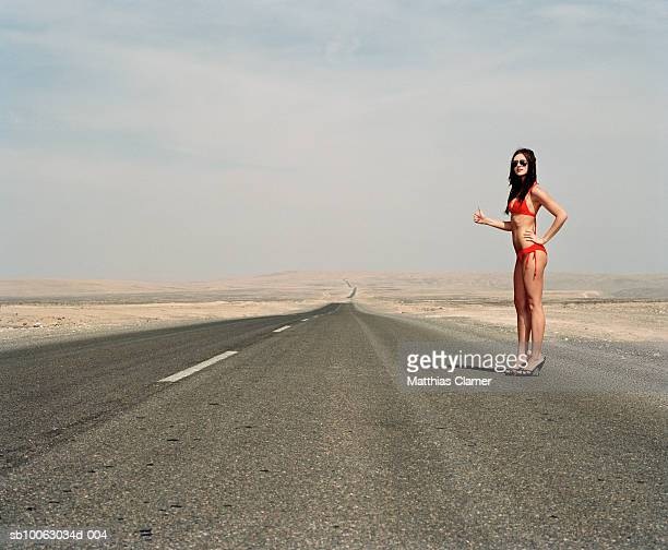 Chile, San Pedro de Atacama, woman wearing bikini hitchhiking in desert