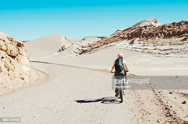Chile, woman riding a mountain bike through the Moon Valley, Atacama Desert