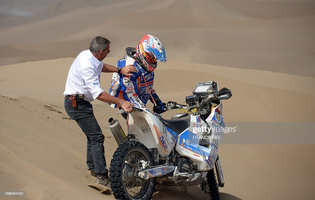 Chilean biker Marco Reinike (R) is helped by the Director of the Dakar Rally Etienne Lavigne after falling during the Dakar 2013 Stage 6 between Arica and Calama, Chile, on January 10, 2013. The rally is taking place in Peru, Argentina and Chile from January 5 to 20.