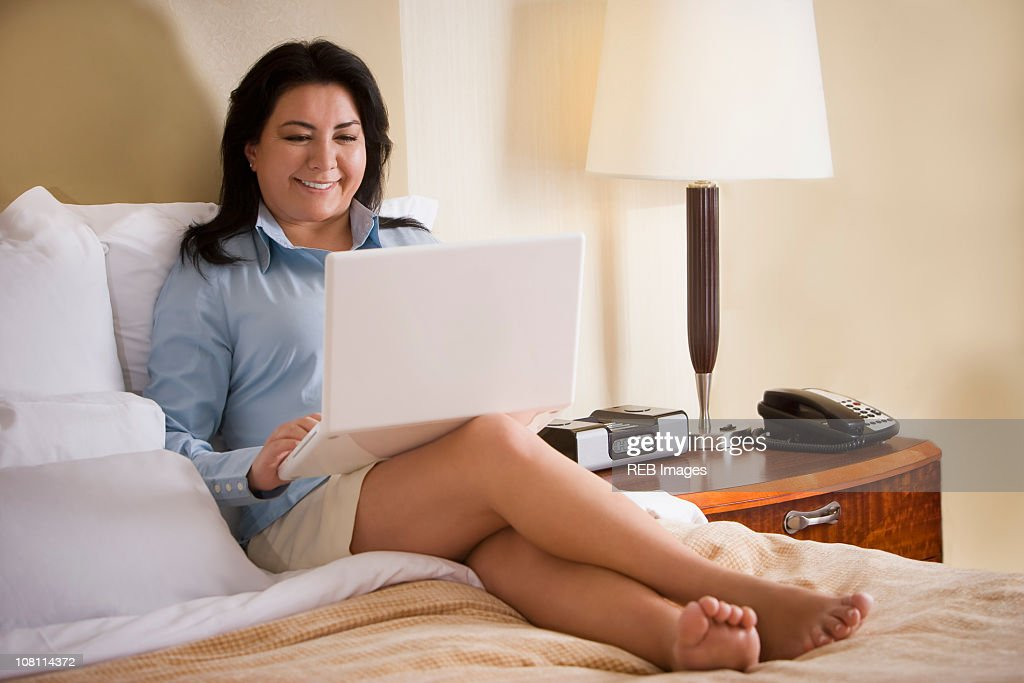 Chilean businesswoman sitting on bed using laptop