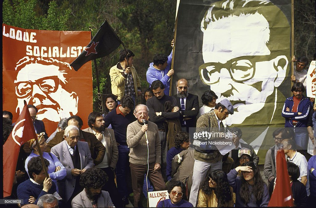 Chilean Ex-Allende Gov't. Cabinet Min. Carlos Briones (C) partly obscured by microphone animated and speaking to crowd during the memorial organized by the Communist and Socialist parties on the 12th anniversary of death of deposed Socialist Pres. Salvadore Allende; also two large posters of the deceased president are on stage.