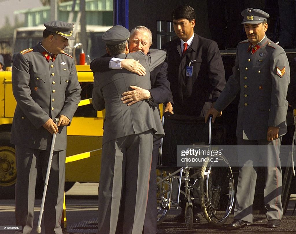 Chilean ex-dictator <a gi-track='captionPersonalityLinkClicked' href=/galleries/search?phrase=Augusto+Pinochet&family=editorial&specificpeople=93107 ng-click='$event.stopPropagation()'>Augusto Pinochet</a> embraces a comrade upon arrival in Santiago, Chile 03 March 2000. Pinochet left Britain 02 March after British Home Secretary Jack Straw announced his decision to free him on health grounds. (ELECTRONIC IMAGE) AFP PHOTO/CRIS BOURONCLE