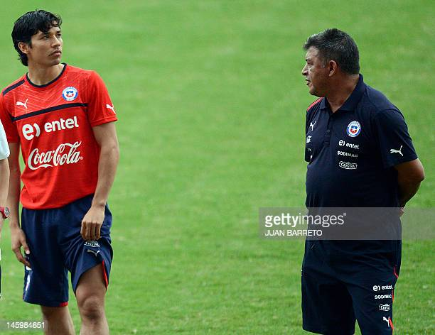 Chilean football team coach Claudio Borghi looks at footballer Matias Fernandez during a training session at the Jose Antonio Anziategui stadium in...