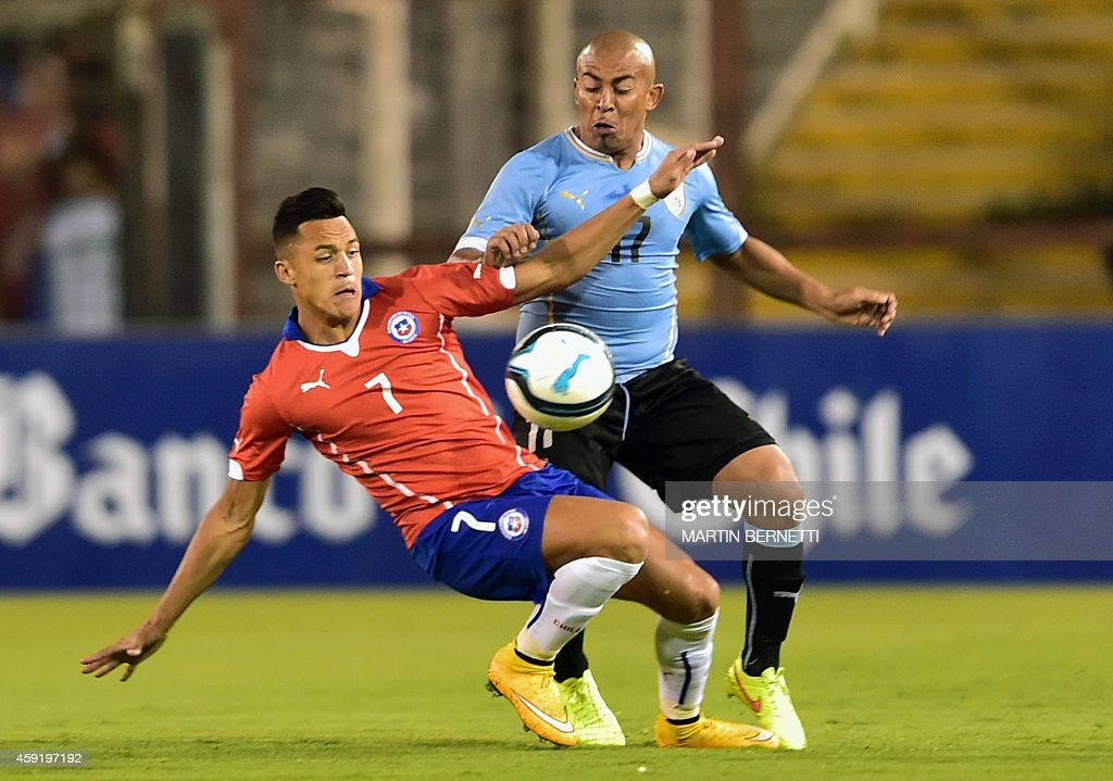 Chilean footballer Alexis Sanchez (L) vies the ball with Uruguay's Carlos Sanchez (R) during a friendly match at the Monumental Stadium in Santiago, November 18, 2014.