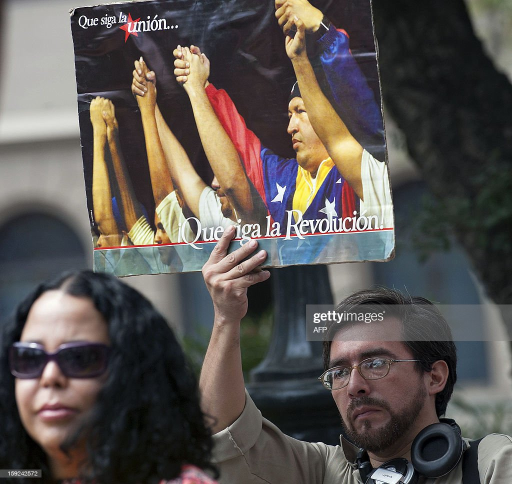 A Chilean holds a poster showing Venezuela's President Hugo Chavez during a ceremony held by Mapuches, Chile's largest indigenous group, for the health of Chavez in Santiago on January 10, 2013. With Chavez ailing and absent, Venezuela's leftist government launches a new presidential term with a display of popular support on the day he was to be inaugurated. The Supreme Court cleared the cancer-stricken president,kwho is recovering from a fourth round of cancer surgery in Havana, to indefinitely postpone his re-inauguration and said his existing administration could remain in office until he is well enough to take the oath. The government has said that he is recovering from complications from surgery, most recently a severe pulmonary infection that had resulted in a 'respiratory insufficiency.' AFP PHOTO/ Claudio Santana. AFP PHOTO /Claudio SANTANA