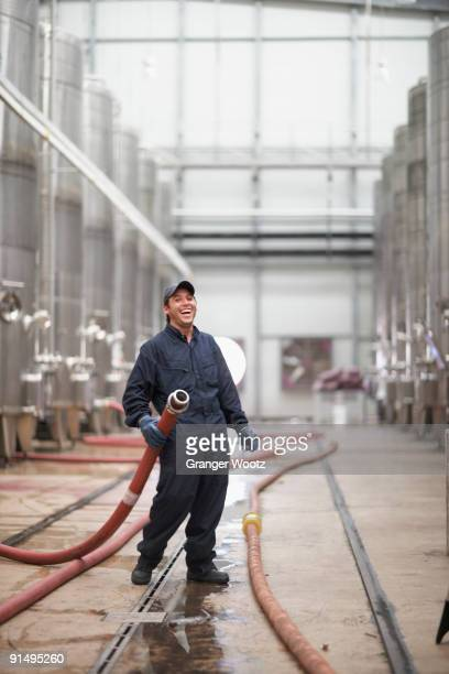 Chilean man holding industrial hose at winery