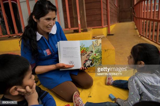 A Chilean Mapuche teacher reads books to Mapuche children at their school in Temulemu Temuco on November 09 2017 The Mapuches which represent about...