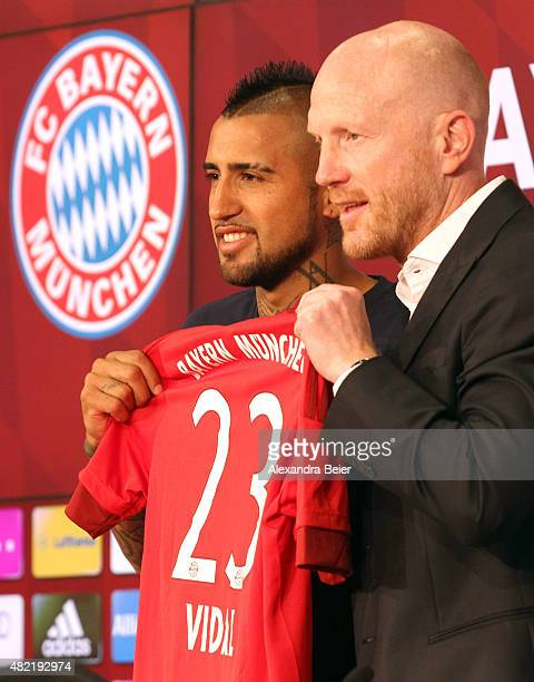 Chilean midfielder Arturo Vidal and FC Bayern Munich sporting director Matthias Sammer hold Viadl's new jersey during a news conference after he...