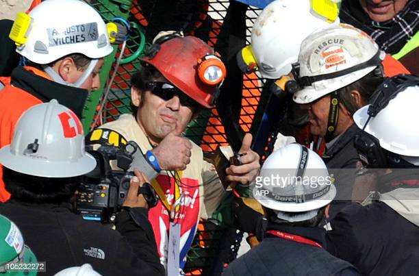 Chilean miner Alex Vega Salazar gives a thumbs up upon exiting the Fenix capsule as the tenth miner to be brought to the surface on October 13 2010...