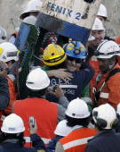Chilean miner Franklin Lobos embraces a rescue member as he exits the Fenix 2 capsule after being brought to the surface from the San Jose mine near...