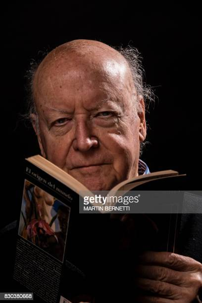 Chilean novelist and journalist Jorge Edwards poses with his book 'The origin of the world' during a photo session in Santiago on August 11 2017...