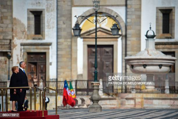 Chilean President Michelle Bachelet and Portuguese President Marcelo Rebelo de Sousa listen to their national anthems at Giraldo square in Evora...