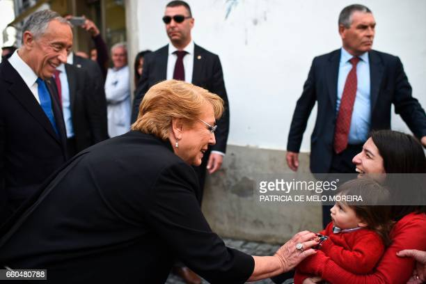 Chilean President Michelle Bachelet and Portuguese President Marcelo Rebelo de Sousa cheer locals as they walk the streets of Evora Alentejo on March...