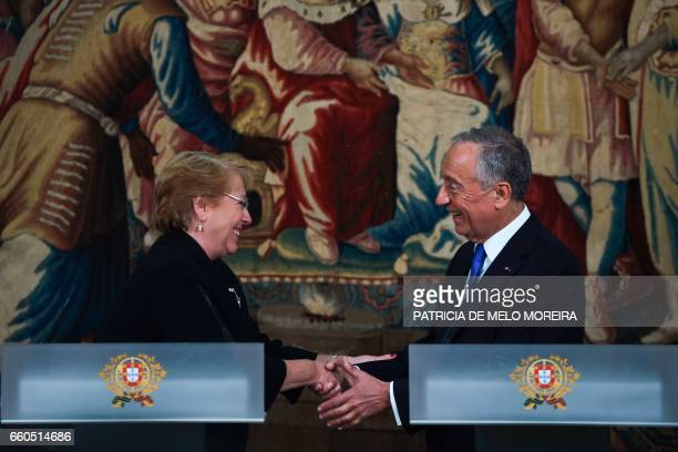 Chilean President Michelle Bachelet shakes hands with Portuguese President Marcelo Rebelo de Sousa at the end of a joint press conference at Sao...