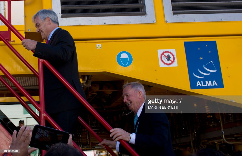 Chilean president Sebastian Pinera (L) and Alma Director Thijs De Graauw (R) climb stairs to see radio telescope antennas at the ALMA (Atacama Large Millimeter/submillimeter Array) project station, in San Pedro de Atacama, some 1500 km north of Santiago, on March 13, 2013. The ALMA, an international partnership project of Europe, North America and East Asia with the cooperation of Chile, is presently the largest astronomical project in the world. Today will be opened 59 of 66 high precision antennas, located at 5000 of altitude in the extremely arid Atacama desert. AFP PHOTO/Martin BERNETTI