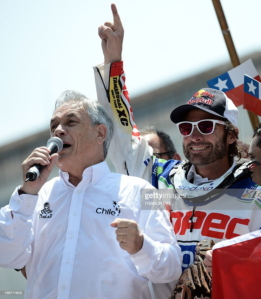 Chilean President Sebastian Pinera (L) speaks next to KTM's rider Chilean Francisco Chaleco Lopez (R) on the podium of the Dakar 2013 in Santiago, Chile on January 20, 2013. KTM's rider French Cyril Despres won the Dakar 2013 ahead of KTM's rider Ruben Faria of Portugal KTM's rider Francisco Chaleco Lopez of Chile.