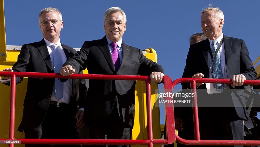Chilean president Sebastian Pinera, with ALMA Director's Thijs De Graauw (R) and General Director ESO, Tim De Zeeuw pose on a radio telescope of the ALMA (Atacama Large Millimeter/submillimeter Array) project station, in San Pedro de Atacama, some 1500 km north of Santiago, on March 13, 2013. The ALMA, an international partnership project of Europe, North America and East Asia with the cooperation of Chile, is presently the largest astronomical project in the world. Today will be opened 59 of 66 high precision antennas, located at 5000 of altitude in the extremely arid Atacama desert. AFP PHOTO/Martin BERNETTI
