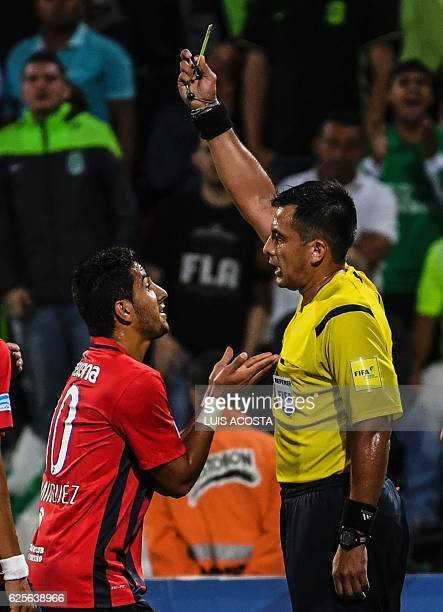 Chilean referee Julio Bascunan shows the yellow card to Paraguay's Cerro Cecilio Dominguez during their e Sudamericana Cup 2016 football second leg...