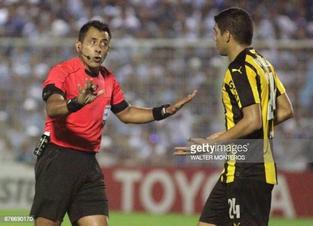 Chilean referee Julio Bascunan speaks to Ivan Villalba of Uruguay's Penarol during their Copa Libertadores football match against Argentina's...