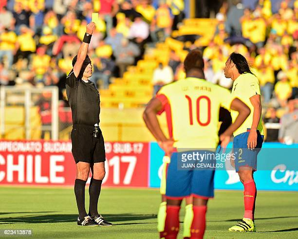 Chilean referee Roberto Tobar shows a yellow card to Ecuador's Arturo Mina during their 2018 FIFA World Cup qualifier football match in Quito on...