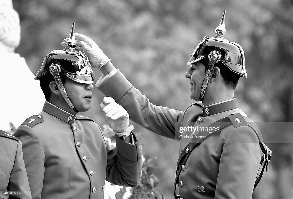 Chilean Soldiers adjust their helmets ahead of a visit by Prince Harry in People's Square at the monument to the founding Father of Chile Bernando O'Higgins on June 27, 2014 in Santiago, Chile. Prince Harry is on a three day tour of Chile after visiting Brazil.