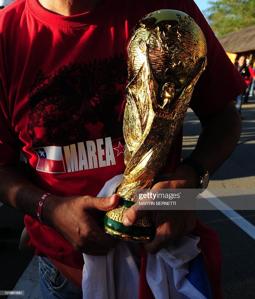 A Chilean supporter holds a fake World Cup trophy during the arrival of the Chilean national football team at the airport in Nelspruit on June 6, 2010. Chile will play against Honduras in their first South Africa 2010 World Cup match on June 16. AFP PHOTO / Martin BERNETTI
