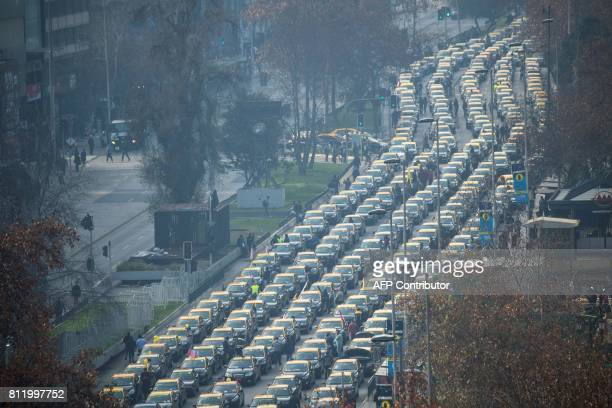 TOPSHOT Chilean taxi drivers demonstrate along Alameda Avenue against US ondemand ride service giant Uber in Santiago on July 10 2017 Uber smartphone...