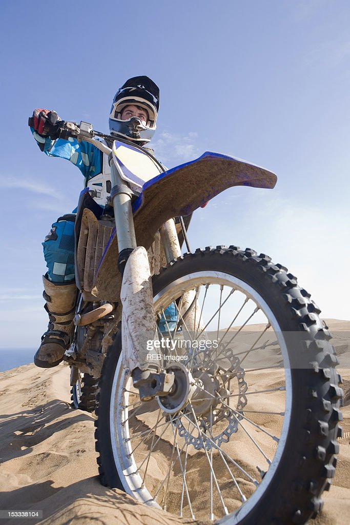 Chilean teenager riding motorcycle on sand dune