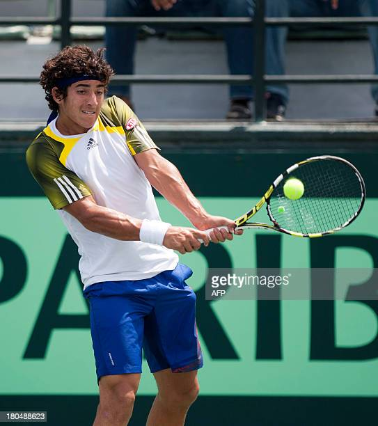 Chilean tennis player Christian Garin returns the ball to Dominican Victor Estrella during their Copa Davis game in Santo Domingo September 13 2013...