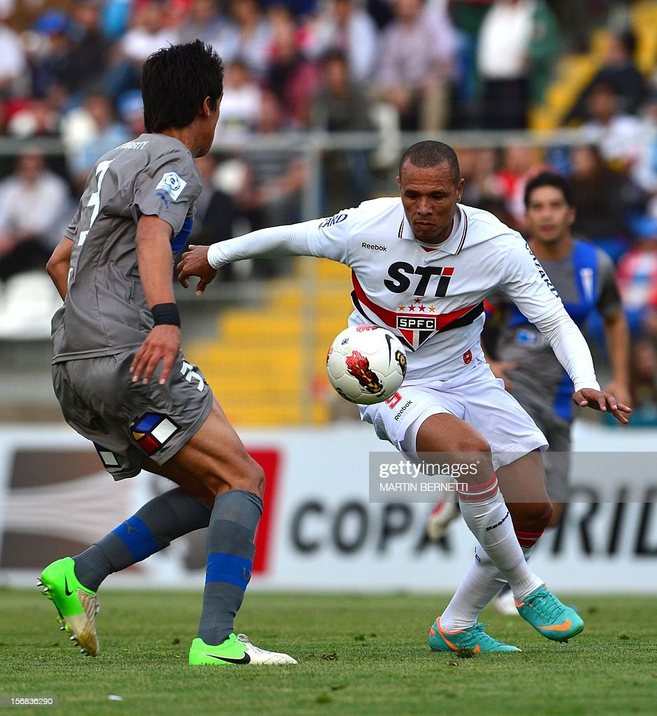 Chilean Universidad Catolica's Enzo Andia (L) vies for the ball with Brazilian Sao Paulo's Fabiano Clamente (R) during their 2012 Copa Sudamericana first leg semifinal football match at San Carlos de Apoquindo stadium in Santiago, Chile, November 22, 2012.