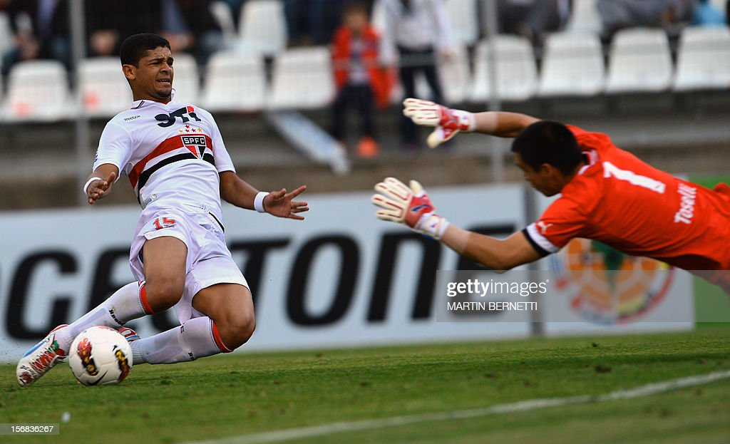 Chilean Universidad Catolica's goalkeeper Christopher Toselli (R) vies for the ball with Brazilian Sao Paulo's Denilson Pereira (L) during their 2012 Copa Sudamericana first leg semifinal football match at San Carlos de Apoquindo stadium in Santiago, Chile, November 22, 2012.