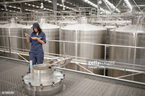 Chilean woman testing wine from vat at winery