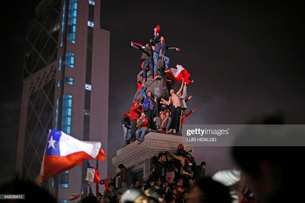 TOPSHOT - Chileans celebrate victory over Argentina in the final match of the Copa America Centenario 2016 in Santiago, Chile, June 26, 2016. Holders Chile stunned Argentina to win the Copa America Centenario in a penalty shoot-out as Lionel Messi's title curse struck again. It was a carbon copy of last year's Copa America final, also won by Chile on penalties after a goalless draw. / AFP / LUIS