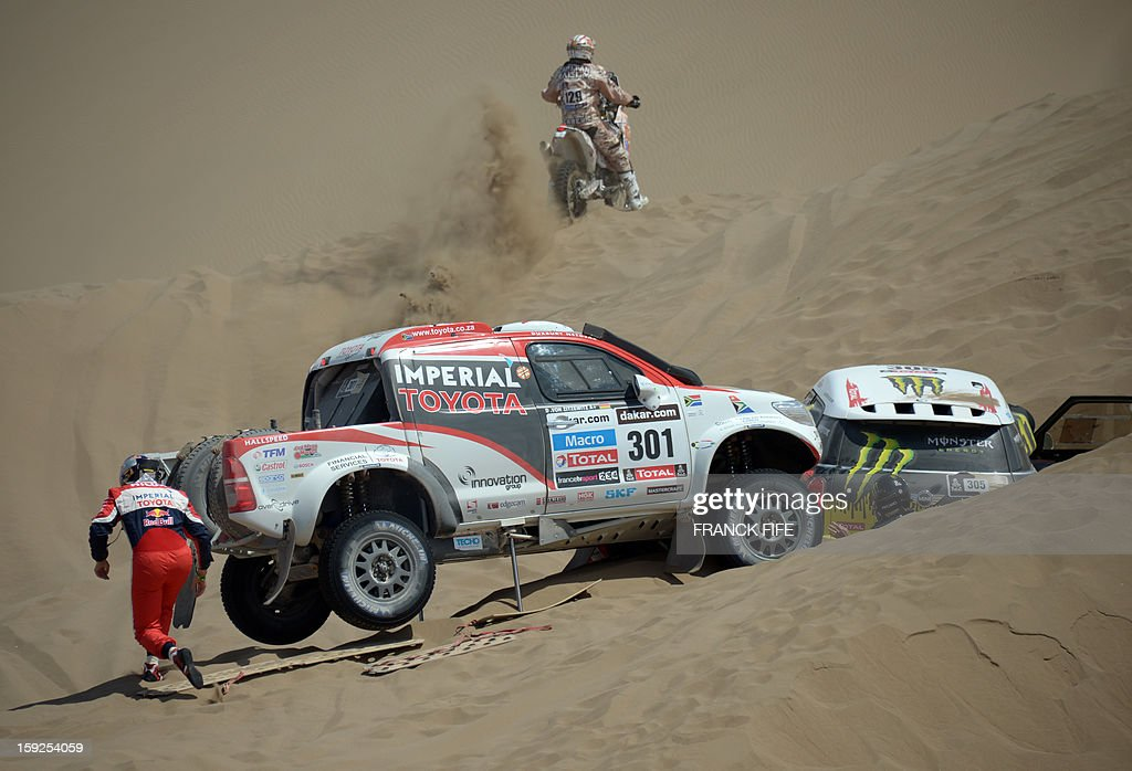 Chiler biker Andres Carevic rides past as Mini's driver Nani Joan Roma (R) of Spain is assisted by Toyota's driver Giniel De Villiers (L) of South Africa during the Stage 6 of the 2013 Dakar Rally between Arica and Calama, Chile, on January 10, 2013. The rally is taking place in Peru, Argentina and Chile from January 5 to 20. AFP PHOTO / FRANCK FIFE