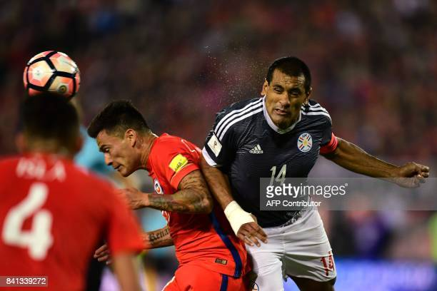 Chile's Charles Aranguiz and Paraguay's Paulo Da Silva vie for the ball during their 2018 World Cup qualifier football match in Santiago on August 31...