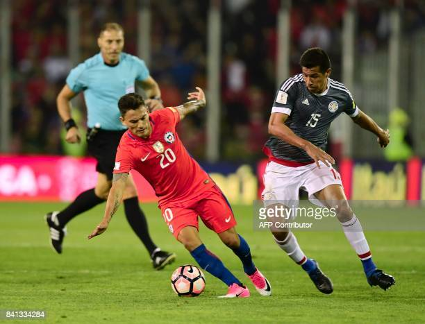Chile's Charles Aranguiz and Paraguay's Victor Caceres vie for the ball during their 2018 World Cup qualifier football match in Santiago on August 31...