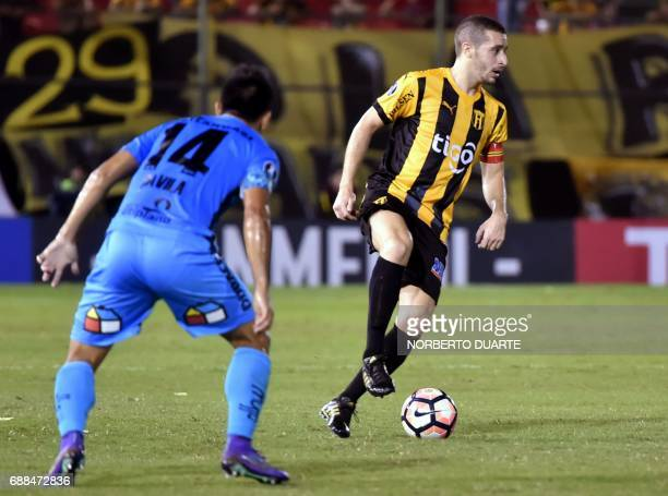 Chile's Deportes Iquique player Misaael Carvajal battles for the ball with Marcelo Palau of Paraguay's Guarani during their Copa Libertadores...