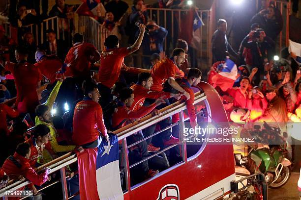 Chile's football team players wave at the crowd from the bus that takes them to La Moneda presidential palace in Santiago on July 4 2015 during the...